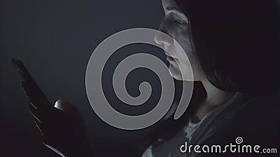 Mooie meisjeszitting bij nacht met telefoon in sociale netwerken stock footage