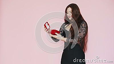 Mooie roodharige meid opent cadeau en bewondert, vreugde Festief gehumeurd op 8 maart Op een roze achtergrond Langzame beweging stock video