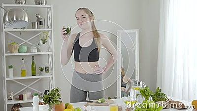 Mooie slanke vrouw die groene kruidencocktail drinkt en glimlacht bij de camera Vertrouwelijk jong Kaukasisch meisje met detox stock videobeelden