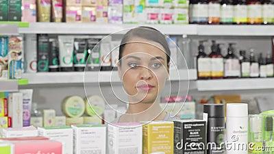 Mooie vrouw die producten onderzoekt die te koop zijn in de lokale apotheek stock footage