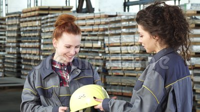 Mooie vrouwelijke fabrieksarbeider die een bouwvakker van haar collega ontvangen stock footage
