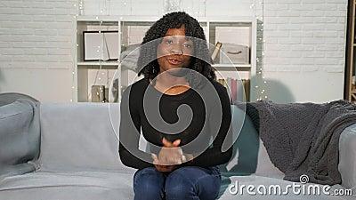 Mooie zwarte dame met krullend haar zit op de grijze sofa en praat stock video