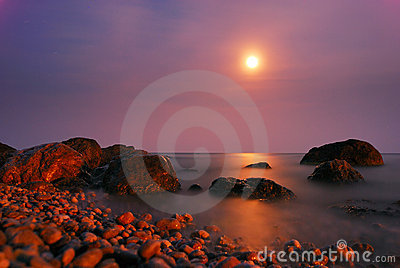Moon path over the night sea with rocks