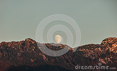 Moon rising over forested mountains at sunset.