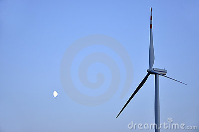 Moon and wind turbine against the blue sky