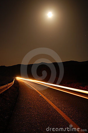 A moonlit road with car trails
