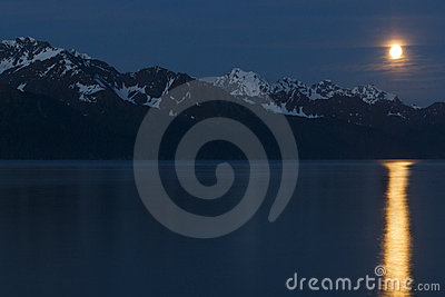 Moonrise over mountains with full moon reflection