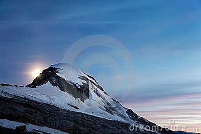 Moonrise over snowed mountain