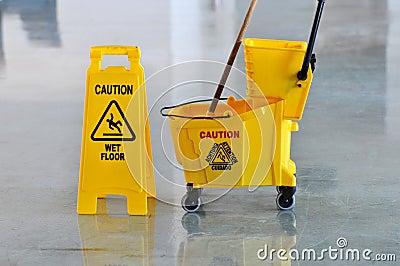Mop, benna e pavimento bagnato di avvertenza