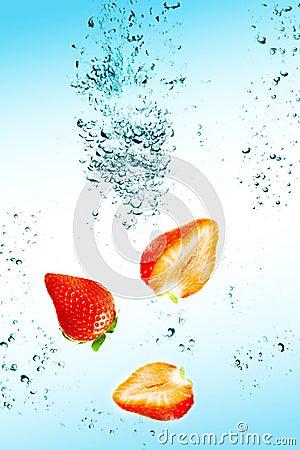A morango está caindo na água com um respingo grande