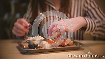 A morena bonita nova da mulher mancha a pasta em uma parte de pão no café Mãos do ` s da mulher do close-up com faca vídeos de arquivo
