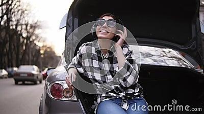 A morena de sorriso escuta a música no fones de ouvido ao sentar-se no tronco aberto do ` s do carro entre a estrada Teclas do te vídeos de arquivo
