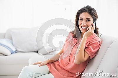 Morenita sonriente que se sienta en su sofá en el teléfono