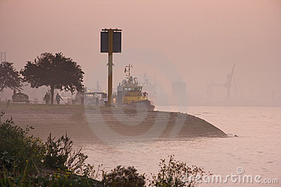 Morning fog at river with ships and industry