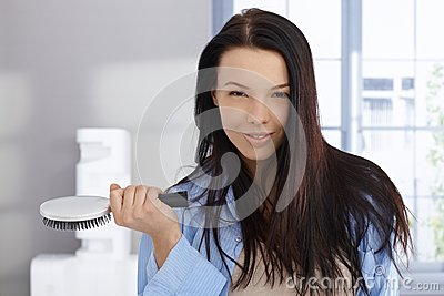 Morning portrait of young woman with hairbrush