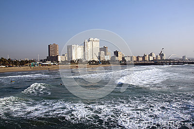 Morning Surfers on Beach Against City Skyline Editorial Photo