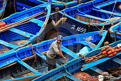 Moroccan Fisherman and blue fishing boats Editorial Stock Photo