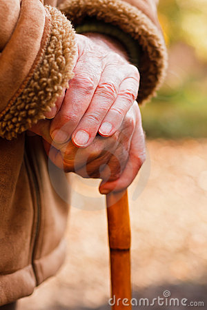 Mãos idosas que descansam na vara de passeio