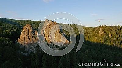Mosca do balão de ar quente através do céu em uma paisagem das montanhas perto das rochas video estoque