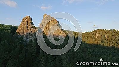 Mosca do balão de ar quente através do céu em uma paisagem das montanhas perto das rochas vídeos de arquivo