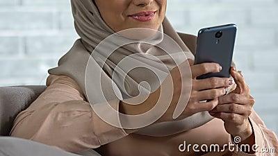 Moslemisches weibliches am Handy zu Hause plaudern, neuen App prüfend, Technologie stock video footage