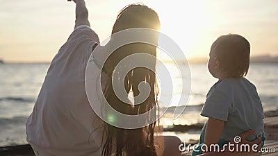 Mostras da mamã ao bebê algo no céu, estando perto do mar no movimento lento vídeos de arquivo