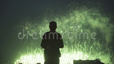Mostre em silhueta o fotógrafo novo que está no telhado com a câmera que olha fogos-de-artifício filme