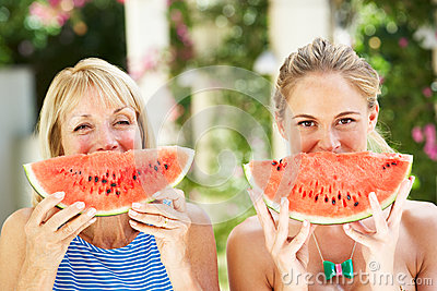 Mother And Adult Daughter Enjoying Water Melon