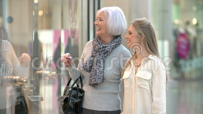 Mother And Adult Daughter In Shopping Mall Together. Mother with adult daughter in shopping mall pausing to look at window display. Shot on Sony FS700 at frame stock video