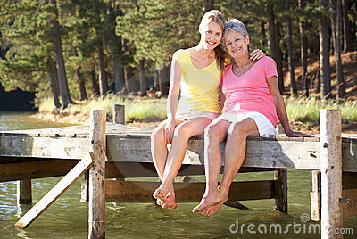 Mother and adult daughter sitting by lake
