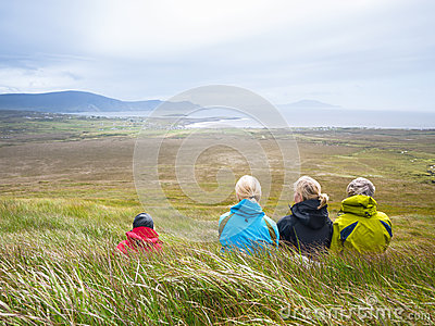 Mother with adult daughters resting on meadow during walk