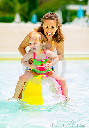 Free Mother And Baby Playing With Beach Ball In Pool Royalty Free Stock Photos - 47531348