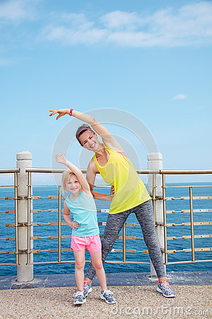 Free Mother And Child In Fitness Outfit Stretching On Embankment Stock Photo - 74858850