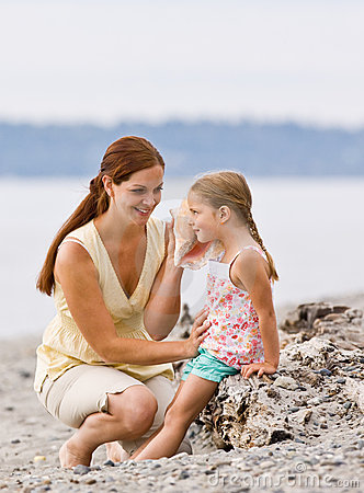 Free Mother And Daughter Listening To Seashell At Beach Stock Photo - 7430390