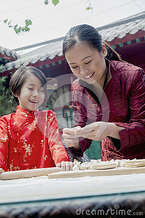 Free Mother And Daughter Making Dumplings In Traditional Clothing Royalty Free Stock Photography - 33394247