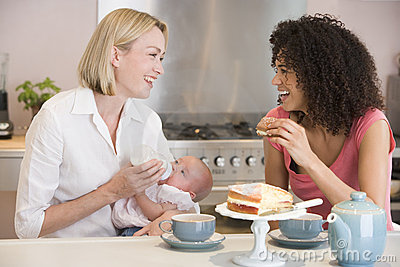 Mother and baby with friend eating cake