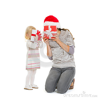 Mother and baby hiding behind Christmas gift boxes
