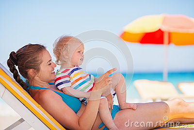 Mother with baby laying on sunbed