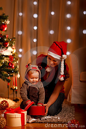 Mother with baby opening gift near Christmas tree