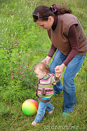 Mother and baby play with ball on grass