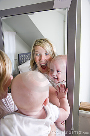 Mother and baby playing in mirror
