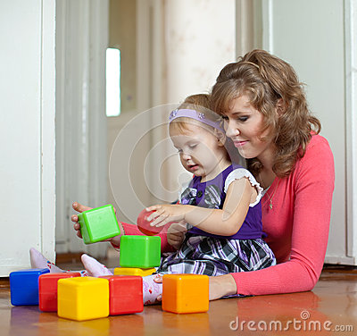 Mother and baby plays with toys