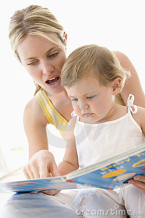 Mother and baby reading book indoors