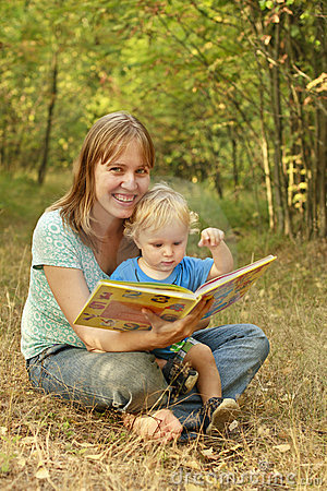 Mother and baby reading book in nature