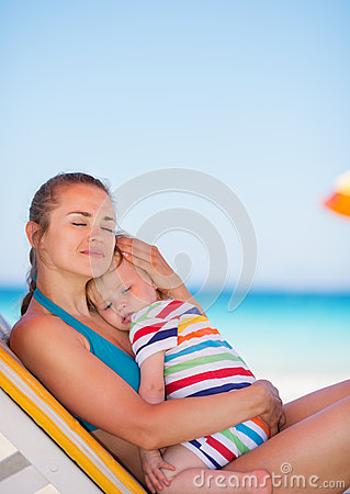 Mother and baby relaxing on sunbed on beach