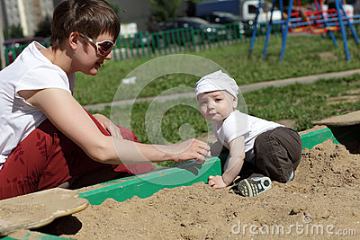 Mother and baby in sandbox