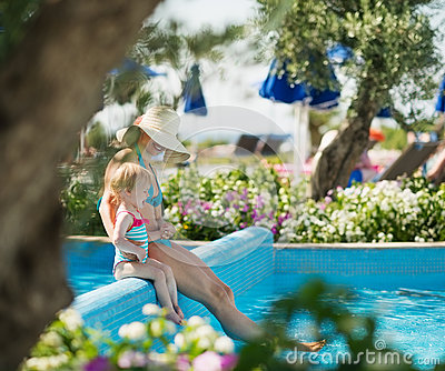 Mother With Baby Sitting On Pool Side Royalty Free Stock Photography - Image: 25470767