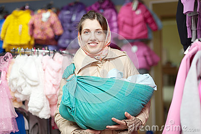 Mother with baby in sling at shop