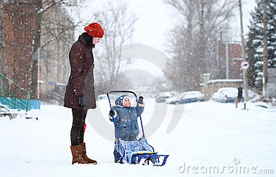 Mother and baby walk in winter with sledges