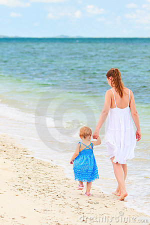 Mother and baby walking along tropical beach